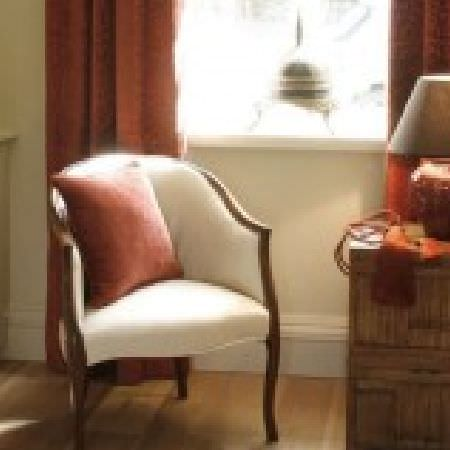 Kestrel Lister -  Banbury Fabric Collection - A plain white armchair with a wooden frame, with plain terracotta coloured curtains and a cushion, and a matching lamp
