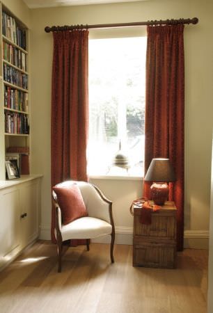 Kestrel Lister -  Banbury Fabric Collection - Plain terracotta curtains and a cushion with a white armchair with a wooden frame, beside a wood cabinet and a lamp