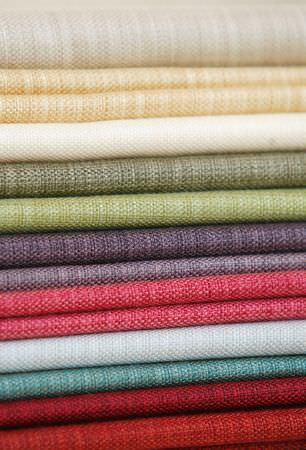 Kestrel Lister -  Celine Co-Ordinate Fabric Collection - A stack of neatly folded plain fabrics in various shades including scarlet, sky blue, pink, grey, green, white and cream