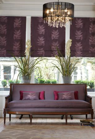Kestrel Lister -  Celine Fabric Collection - A plain purple sofa with a dark wood frame, 4 purple and dark pink cushions, and dark purple leaf print blinds