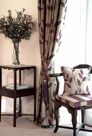 Kestrel Lister -  Gardenia Fabric Collection - Aubergine and putty coloured leaves and stripes on curtains, scatter and seat cushions, with a dark wood chair and table