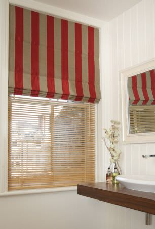 Kestrel Lister -  Gardenia Stripe Fabric Collection - A vertically striped red and beige window blind, with a wooden slatted blind, in a bathroom with a dark wood counter