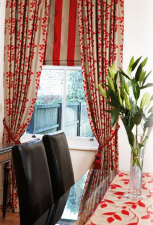 Kestrel Lister -  Gardenia Trellis Fabric Collection - A red and beige striped blind, matching leaf print curtains and a table runner on a glass dining table with black chairs