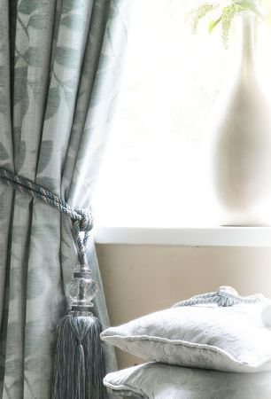 Kestrel Lister -  Henley Fabric Collection - A duck egg blue coloured tieback around matching lustrous leaf print curtains, beside two cushions and a white vase