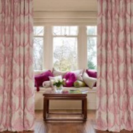 Kestrel Lister -  Leila Fabric Collection - Pale pink and white patterned curtains, a white window seat with white and magenta scatter cushions, and a wooden table