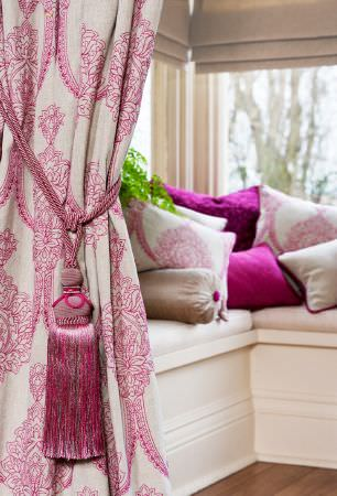 Kestrel Lister -  Leila Fabric Collection - A pink and white patterned curtain with a tieback, and various lustrous, plain and patterned pink, white and silver cushions