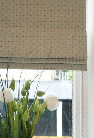 Kestrel Lister -  Roma Fabric Collection - A bunch of flowers beneath a window blind with a very small, subtle geometric pattern in black, pastel blue and light grey