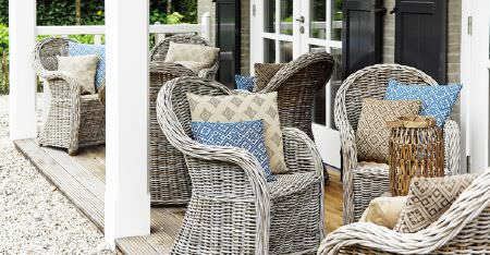 Kobe -  Ambiance Fabric Collection - A patio with 7 grey wicker armchairs, each with two patterned scatter cushions, either in cream, light brown or blue