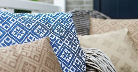 Kobe -  Ambiance Fabric Collection - Light brown, blue, white and cream patterned square scatter cushions placed on grey wicker chairs