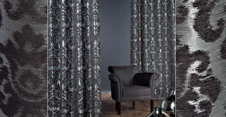 Kobe -  Ashley Fabric Collection - Two dark shades of silvery grey making up ornately patterned curtains, behind a dark grey coloured armchair