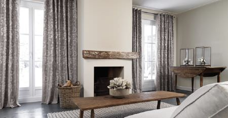 Kobe -  Camden Fabric Collection - Grey patterned curtains, 2 wooden tables, a plain white sofa, a chunky white rug, a wicker basket, and a bowl of flowers