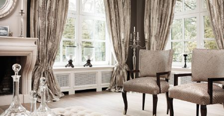 Kobe -  Dauphine Fabric Collection - 2 subtly patterned champagne coloured armchairs with dark wood frames, with patterned curtains and a tall candelabra