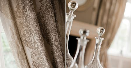 Kobe -  Dauphine Fabric Collection - Three glass decanters in front of cream coloured curtains featuring an ornate light brown pattern