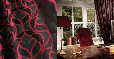 Kobe -  Dauphine Fabric Collection - A wooden desk with a ruby coloured padded chair, a matching desk lamp, and luxurious red and black patterned curtains