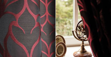 Kobe -  Dauphine Fabric Collection - Wooden frames and ornaments behind curtains made with a luxurious deep ruby coloured pattern on a charcoal background