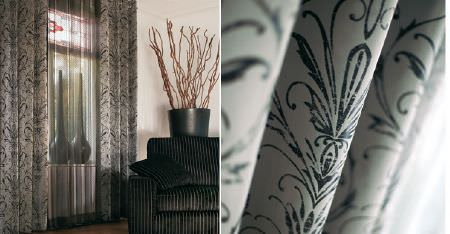 Kobe -  Esmeraldo Fabric Collection - Dark and light grey patterned curtains, sheer curtains, two tall vases, and a black and grey striped sofa and cushion