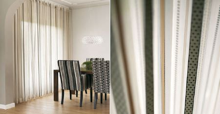 Kobe -  Esmeraldo Fabric Collection - A table with grey, black and white dotted and striped chairs, beside sheer striped curtains in white, biscuit and olive green