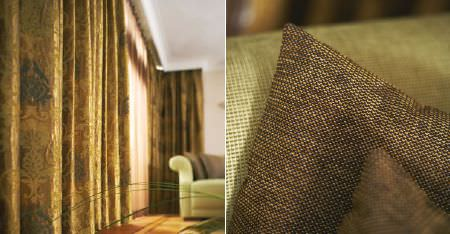 Kobe -  Esmeraldo Fabric Collection - A sofa and cushions woven in plain light green and dark brown, with grand, patterned, warm gold coloured curtains