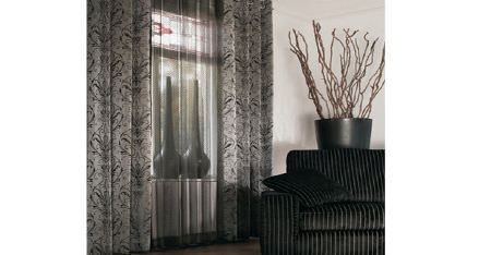 Kobe -  Esmeraldo Fabric Collection - Two tall vases behind two sets of sheer and patterned dark grey curtains, with a black and grey striped sofa and cushion