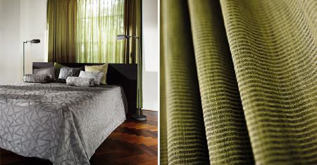 Kobe -  Expression Fabric Collection - Sheer curtains striped in grass and olive shades of green, behind a bed with a black headboard and patterned grey bedding
