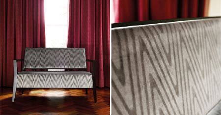 Kobe -  Expression Fabric Collection - Rich claret coloured curtains behind a black framed sofa upholstered with zigzag patterned fabric in two shades of grey