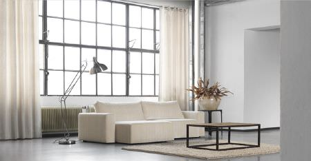 Kobe -  Inoxy Fabric Collection - A chalk white sofa, plain white curtains, a large white rug, wood coffee and side tables, a silver floor lamp, and a vase