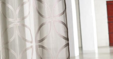 Kobe -  Inoxy Fabric Collection - White pillars behind a swathe of ivory coloured fabric featuring lustrous light silver coloured stylised leaf patterns