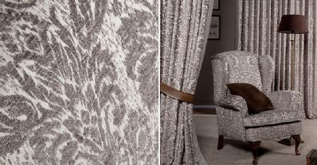 Kobe -  Jockey Fabric Collection - Blurred but intricate patterns in light grey and white, on a padded armchair and curtains, with a brown cushion and lampshade