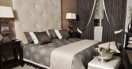 Kobe -  Leonardo CS Fabric Collection - A cream headboard behind a bed with scatter cushions, a patterned duvet, a throw, 2 sets of dark grey curtains, and lamps