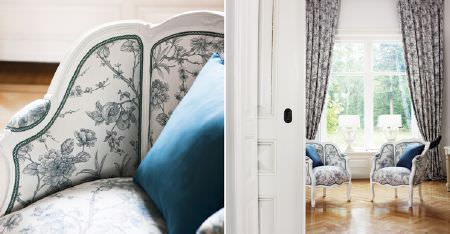 Kobe -  Louvre Fabric Collection - Two white framed tub style armchairs padded with blue-grey and white floral fabric, with matching curtains and blue cushions
