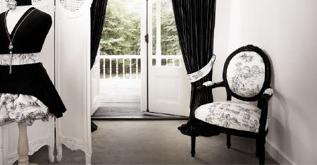 Kobe -  Louvre Fabric Collection - Black curtains, a black framed armchair with a floral monochrome seat and back, a matching tieback, and a dress mannequin