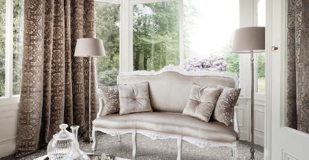 Kobe -  Louvre Fabric Collection - An ornate white frame on an oyster coloured sofa, with 4 scatter cushions, brown and gold patterned curtains, and two lamps