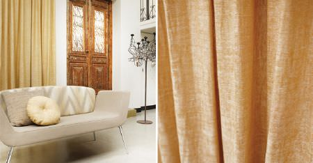 Kobe -  Maroa Fabric Collection - Semi-plain cork and honey coloured curtains behind a retro cream sofa with a zigzag patterned back, and two cushions