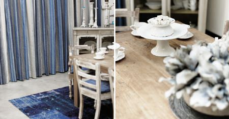 Kobe -  Maroa Fabric Collection - A wooden table, distressed chairs with blue seat cushions, a navy rug, white, grey and blue curtains, and white crockery