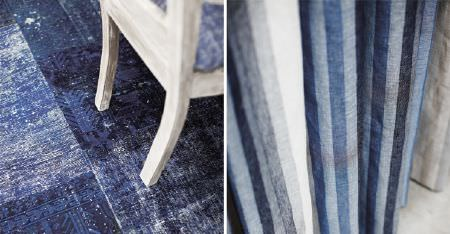 Kobe -  Maroa Fabric Collection - Various shades of blue, grey and white making up vertically striped curtains, with a white chair on a distressed blue rug