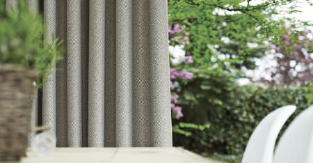 Kobe -  Motion Fabric Collection - Light grey curtains hanging outdoors, printed with a very small, incredibly subtle white dot pattern