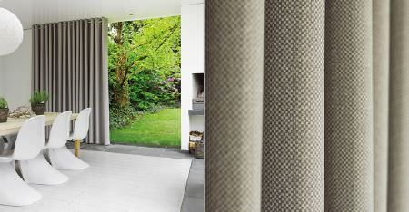 Kobe -  Motion Fabric Collection - Off-white and light grey woven curtains, a large white rug, modern white chairs, a wooden table, flower pots and a garden