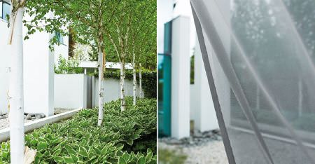 Kobe -  Motion Fabric Collection - An outdoor garden scene draped with a swathe of plain, sheer, light ash grey coloured fabric