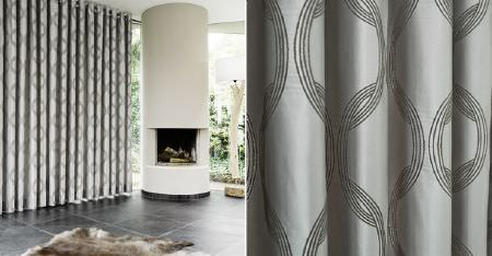 Kobe -  Motion Fabric Collection - A fireplace in a round chimney, lustrous grey curtains featuring an interlocking circle pattern, and an animal fur rug