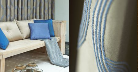 Kobe -  Motion Fabric Collection - A rustic wood bench with plain and slightly textured, patterned champagne and cobalt blue coloured cushions and curtains