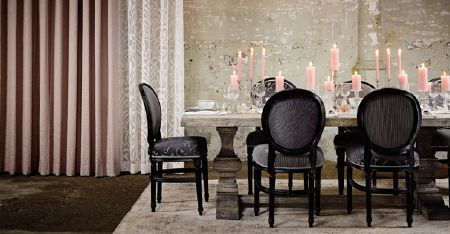 Kobe -  Mystic Fabric Collection - Luxurious dark grey fabrics on ornate black framed armchairs, with a large stone table, candles, and pink and white curtains