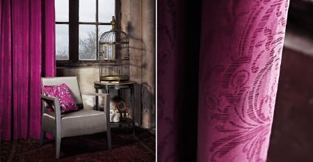 Kobe -  Mystic Fabric Collection - Subtle patterns on bright cerise fabric curtains, with a plain silvery grey armchair, a patterned cushion and a birdcage