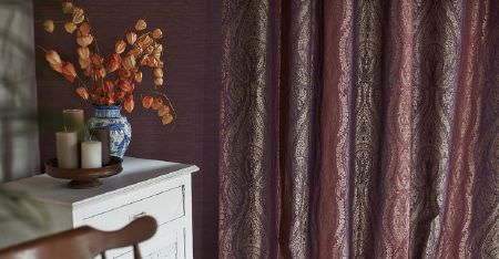 Kobe -  Nomad Fabric Collection - Luxurious, shimmering, subtly patterned curtains in gold, pink and purple shades, with a chair, and white chest of drawers