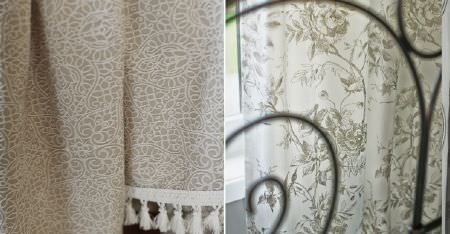 Kobe -  Nomad Fabric Collection - Light grey and white floral curtains, a black metal bed frame, and subtly patterned beige fabric with a cream tassel trim