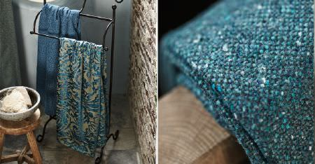 Kobe -  Nomad Fabric Collection - 3 patterned and speckled, woven fabrics in denim blue and turquoise shades, draped over wood and a towel rail, with a stool