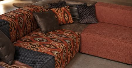 Kobe -  Nomad Fabric Collection - Four scatter cushions on a modular corner sofa made up of dark brown, paprika, patterned slate and tribal print sections