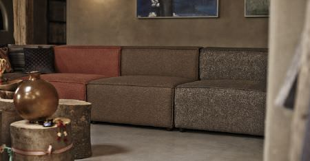 Kobe -  Nomad Fabric Collection - A modular sofa with plain and semi-plain brown and paprika coloured segments, with a cushion, tree stump tables and a vase