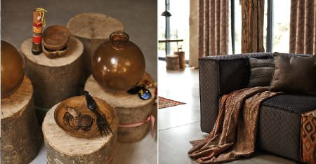 Kobe -  Nomad Fabric Collection - Bowls and round vases on wooden tree stump tables, with a dark brown sofa, scatter cushions and a richly patterned throw