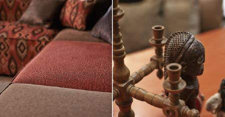 Kobe -  Nomad Fabric Collection - A wooden tribal statue and candelabra, with a brown, red and tribal patterned modular corner sofa, and matching cushions