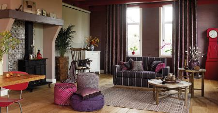 Kobe -  Nomad Fabric Collection - A dark grey striped sofa, a grey rug, pink, purple and grey round footstools, dark curtains, tables, and a rocking chair